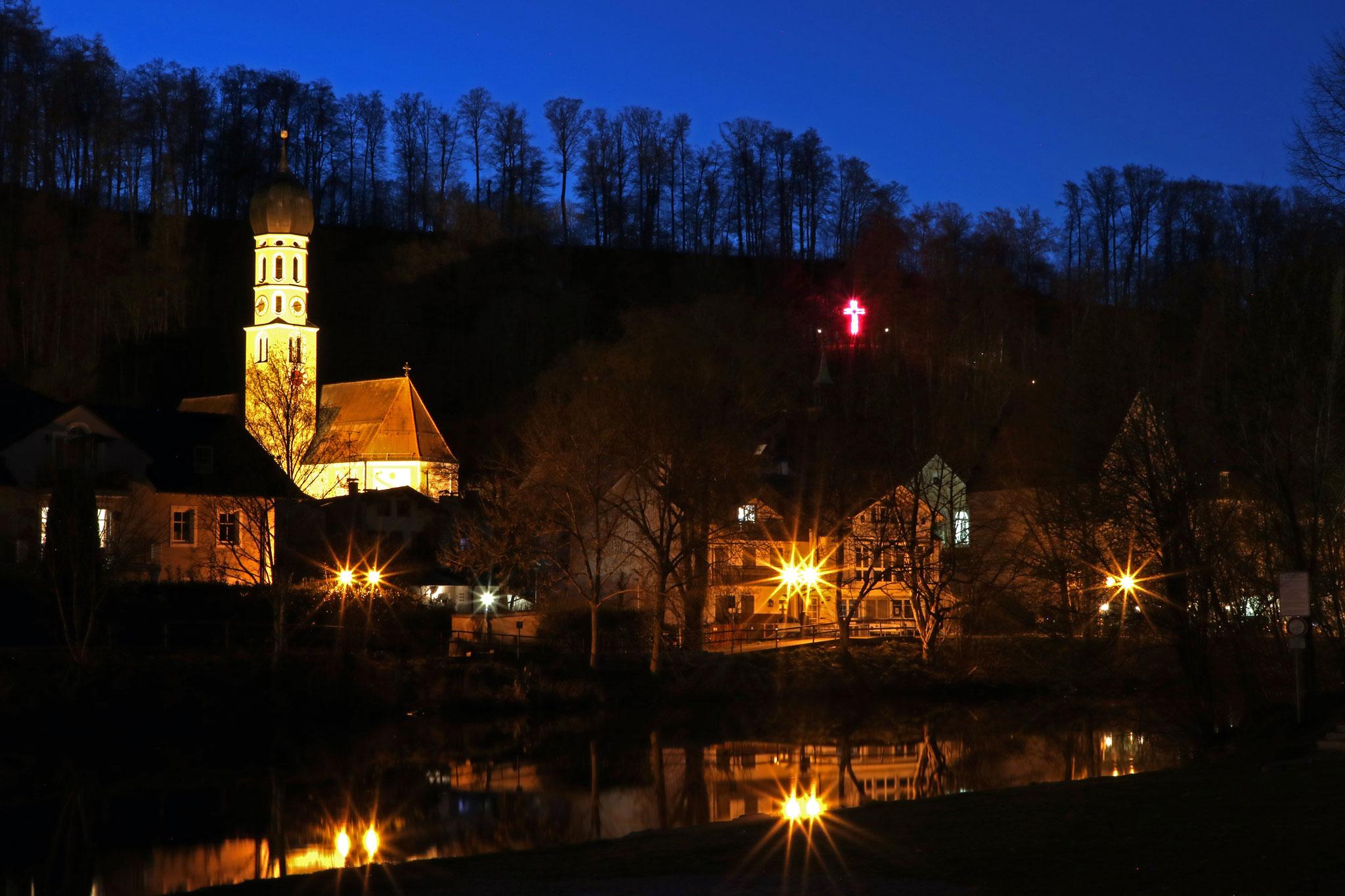 Wolfratshausener Altstadt mit beleuchtetem Kreuz im Bergwald von Hubert Blockinger